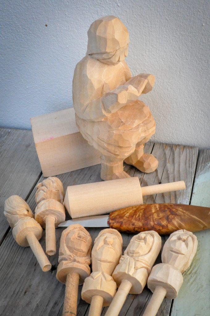 Sittende kone og noen korktryner under arbeid. Trefigur, lind, spikke, kniv. Arbeid av Rita Renton.